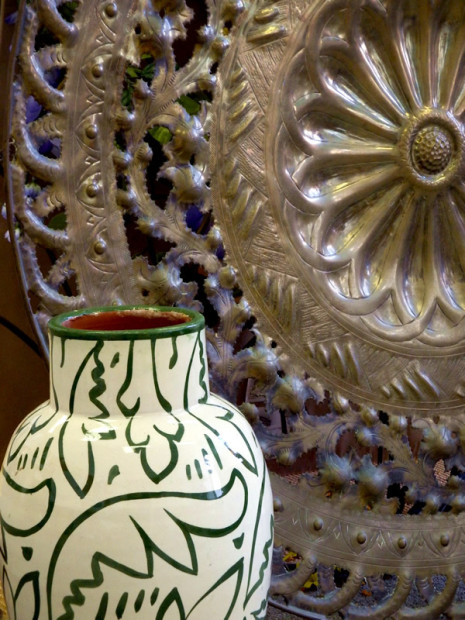 cream colored vase with green decorative pattern and large brass platter